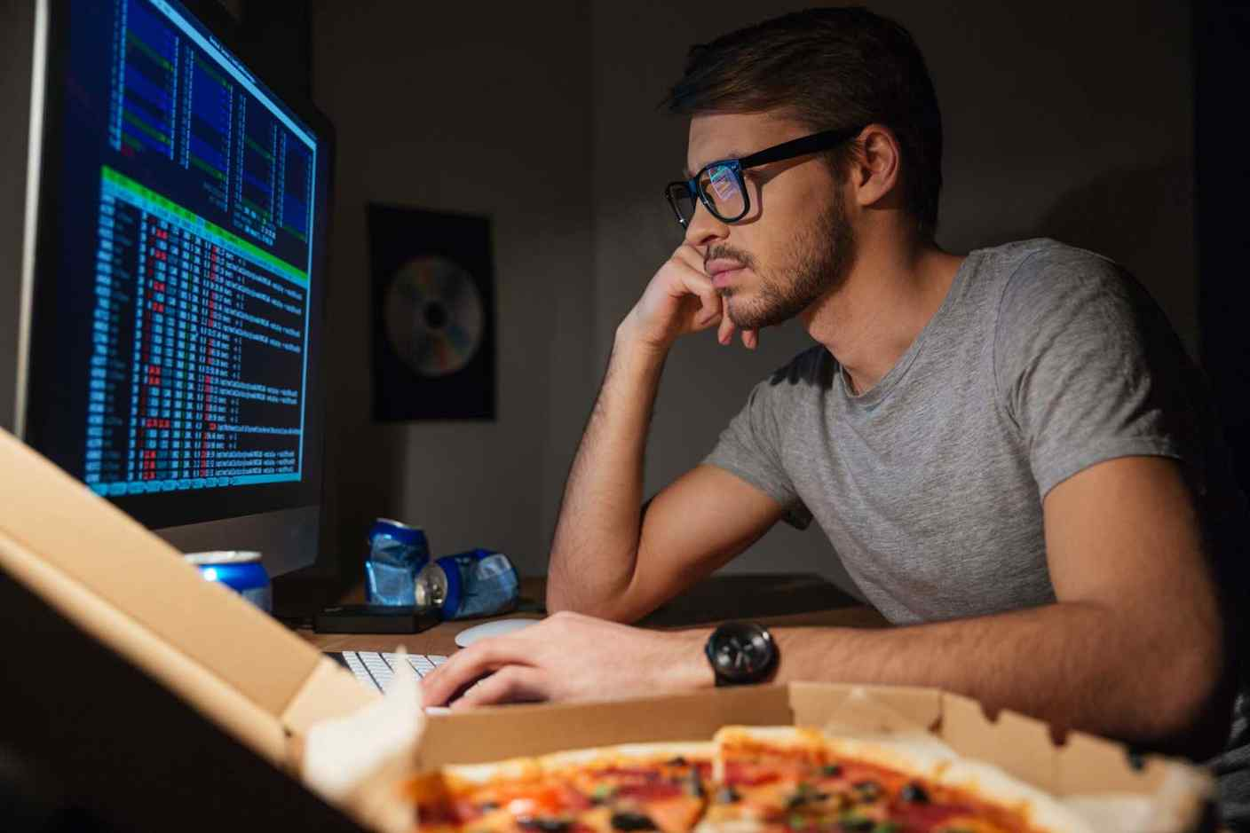 Job cliche: programmer with Pizza in the dark at work