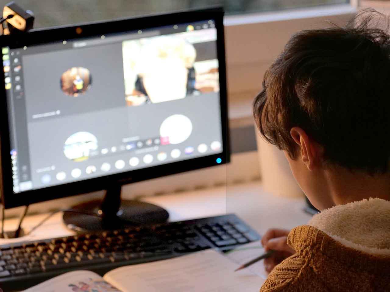 Homeschooling - Kind vor Computer und einem Buch