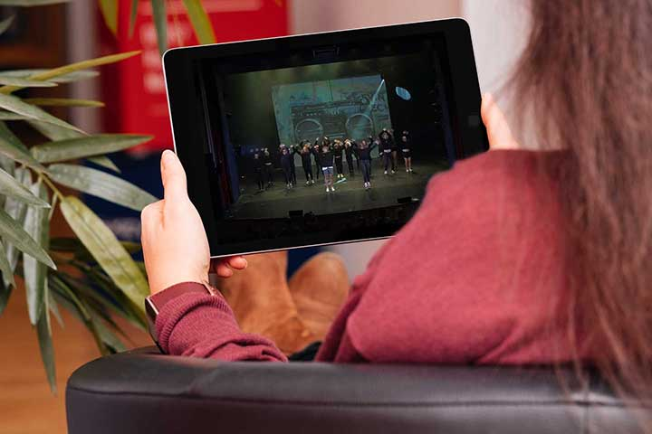 Woman sit comfortably and watch a live show on a mobile device