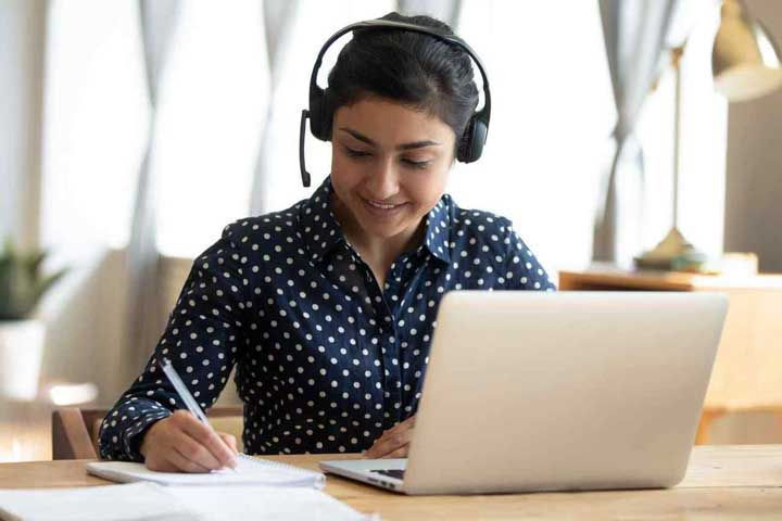 Woman with headset working on laptop in home office