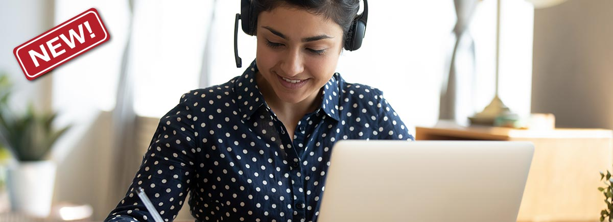 Woman with headset sits in front of a laptop and works